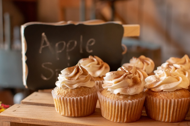 Apple spice cupcakes for a fall wedding. Cupcakes are decorated with a swirled buttercream frosting and dusted with cinnamon.